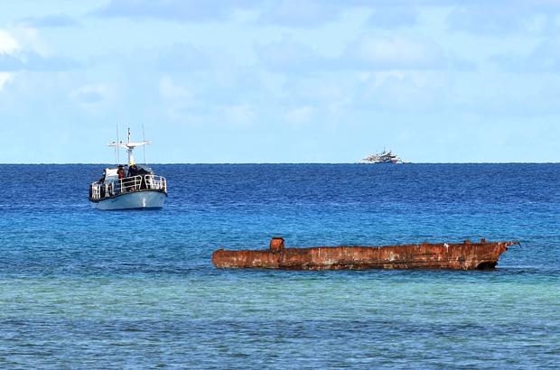 Uma embarcação de pesquisa (esq.) e um barco filipino (dir. no fundo) ancorado perto das Ilhas Thitu no Mar do Sul da China em 21 de abril de 2017 (Ted Aljibe/AFP/Getty Images)