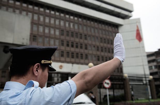 Um policial chinês gesticula em frente do Tribunal Intermediário de Xangai em 8 de agosto de 2014 (Johannes Eisele/AFP/Getty Images)