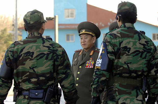 Kim Yong-chol (centro) caminha próximo de soldados sul-coreanos após um diálogo entre generais coreanos no lado sul da vila de armistício de Panmunjom, na Zona Desmilitarizada, em 14 de dezembro de 2007 (Jung Yeon-je/AFP/Getty Images)