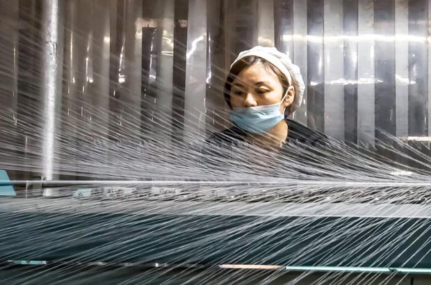 Uma chinesa trabalha numa fábrica têxtil em Nantong, na província de Jiangsu, Leste da China em 10 de dezembro de 2016 (STR/AFP/Getty Images)