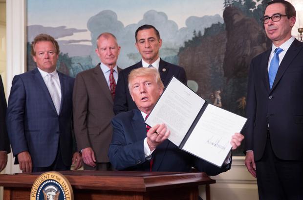 O presidente norte-americano Donald Trump assina um memorando para investigar as práticas de comércio da China, na Casa Branca em Washington, D.C., em 14 de agosto de 2017 (Chris Kleponis/Getty Images)