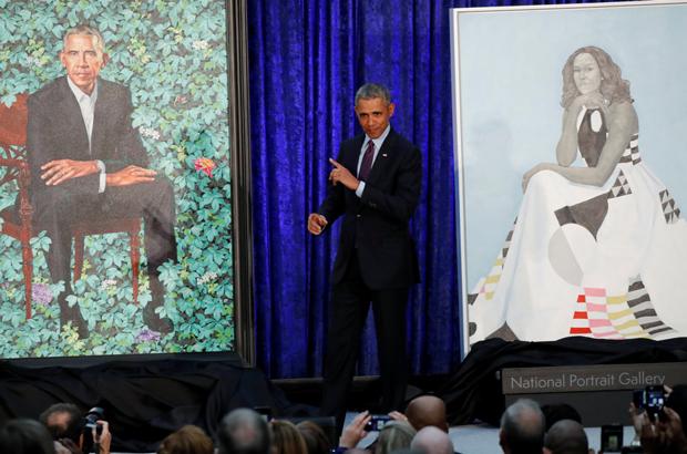 O ex-presidente norte-americano Barack Obama entre seu retrato e o da ex-primeira-dama Michelle Obama durante uma cerimônia de apresentação das pinturas na Galeria de Retrato Nacional do Smithsonian, em Washington, D.C., em 12 de fevereiro de 2018 (Jim Bourg/Reuters)