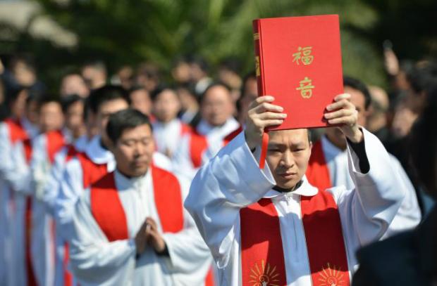 """Funeral do bispo Joseph Fan Zhongliang, ex-líder da Igreja Católica clandestina em Xangai, em 22 de março de 2014. Muitos católicos chineses, em desafio ao regime chinês, frequentam as """"igrejas domésticas"""" clandestinas em vez das igrejas da Associação Católica Patriótica da China (ACPC), autorizadas pelo regime (Peter Parks/AFP/Getty Images)"""