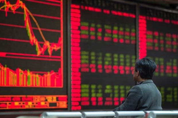 Investidor olha preços das ações nas telas de uma empresa de corretagem em Pequim, em 22 de março de 2016 (Fred Dufour/AFP/Getty Images)