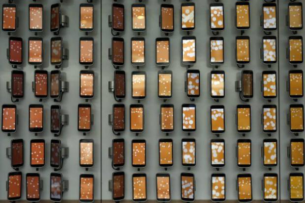 Smartphones pendurados em uma parede do Mobile World Congress (MWC, da sigla em inglês), a maior feira de smartphones do mundo, em Barcelona, na Espanha, em 28 de fevereiro de 2018 (P. Barrena/AFP/Getty Images)