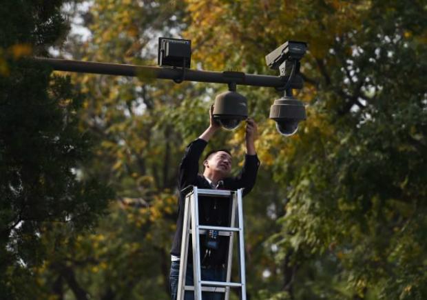 Funcionário ajusta câmeras de segurança instaladas na Praça Tiananmen em Pequim, em 30 de setembro de 2014 (Greg Baker/AFP/Getty Images)
