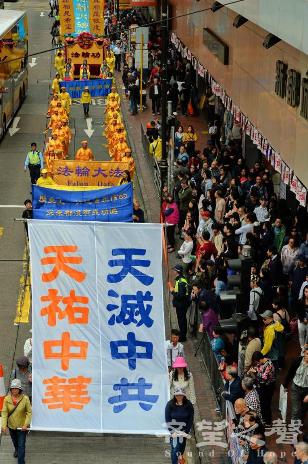 """Participantes de desfile carregam bandeira que diz: """"Os céus protegerão a terra da China. Os céus irão eliminar o Partido Comunista Chinês """" (Song Bilong/Epoch Times)"""