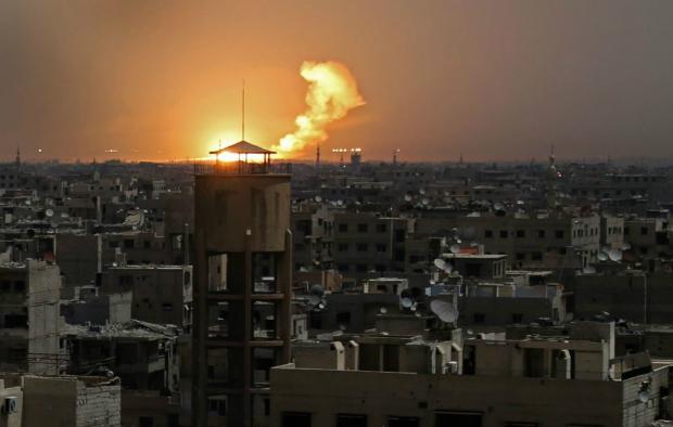 Foto tirada na quarta-feira (28) mostra fogo e fumaça no horizonte após um ataque de foguete contra al-Shaffuniyah, em Guta Oriental, nos arredores de Damasco, capital síria (Ammar Suleiman/AFP/Getty Images)