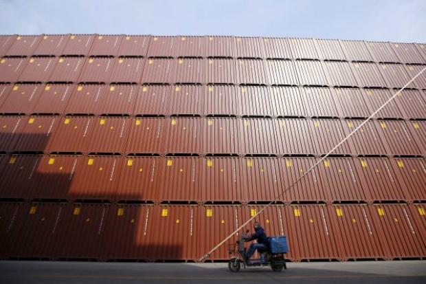 Homem em uma motocicleta passa em frente a contêineres desembarcados no porto de Xangai, na China, em 17 de fevereiro de 2016 (Aly Song/Arquivo)