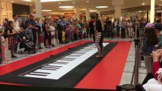 Casal dança música em piano gigante enquanto audiência aplaude