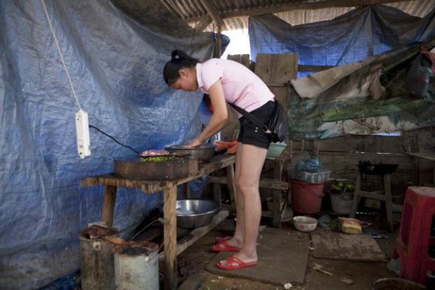 Mulher que foi despejada de sua casa para dar espaço à construção de um ginásio de esportes financiado pela empresa Loudi City Construction and Investment Co. cozinha em um albergue na província de Hunan, na China, em 17 de junho de 2011 (Adam Dean/Bloomberg/Getty Images)
