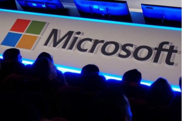 Usuários internacionais ouvem discurso em frente ao logotipo da Microsoft durante a feira de tecnologia Computex em Taipei, em 4 de junho de 2014 (Sam Yeh/AFP/Getty Images)