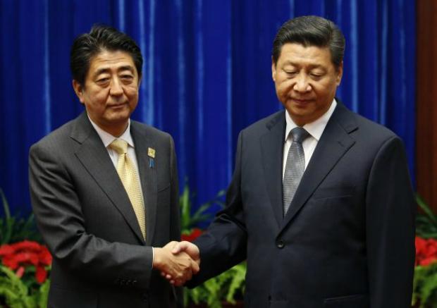 Primeiro-ministro do Japão, Shinzo Abe (esq.) aperta a mão do líder chinês Xi Jinping durante reunião no Grande Salão do Povo em Pequim, na China, em 10 de novembro de 2014 (Kim Kyung-Hoon-pool/Getty Images)