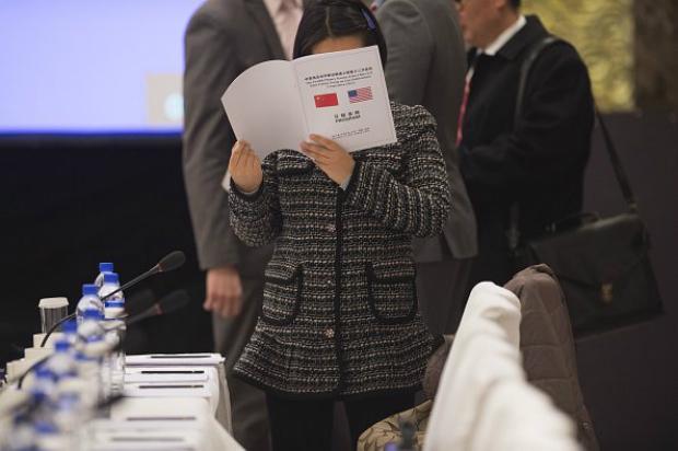 Mulher consulta programação antes do discurso do vice-chefe de Missão da Embaixada dos EUA, Dan Kritenbrink, e do vice-ministro das Relações Exteriores da China, Liu Zhenmin, em Pequim, em 3 de dezembro de 2014 (Fred Dufour/AFP/Getty Images)