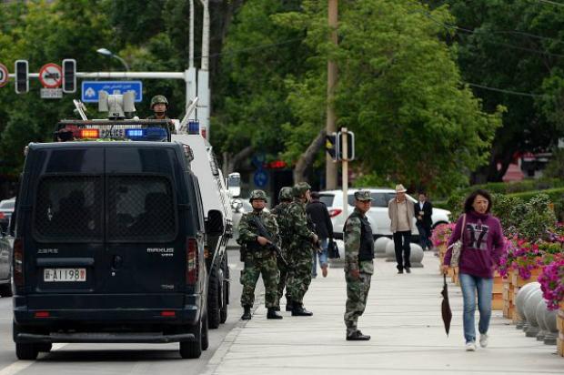 Agentes da polícia paramilitar chinesa vigiam rua em Urumqi, Xinjiang, em 23 de maio de 2014 (Ko Chai Hin/AFP/Getty)