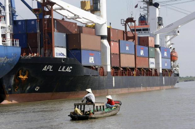 Pequeno barco navega próximo de um porto de contêineres recém construído na cidade de Ho Chi Minh, no Vietnã, em 21 de dezembro de 2006 (Hoang Dinh Nam/AFP/Getty Images)