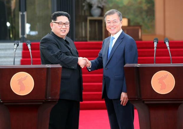 Líder norte-coreano Kim Jong-un e o presidente sul-coreano Moon Jae-in apertam as mãos depois de anunciar a Declaração de Panmunjom para a Paz, a Prosperidade e a Unificação da Península Coreana em frente à Casa da Paz em 27 de abril de 2018 em Panmunjom (Korea Summit Press Pool/Getty Images)