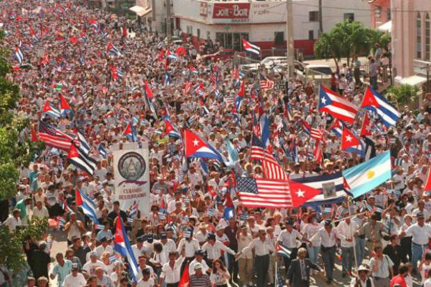 Dezenas de milhares de pessoas, em sua maioria cubanos que vivem nos EUA, caminham pelas ruas de Little Havanna em Miami, Flórida, em protesto contra o regime dos Castro e em apoio às sanções contra o regime, em dezembro de 1994 (Doug Collier/AFP/Getty Images)