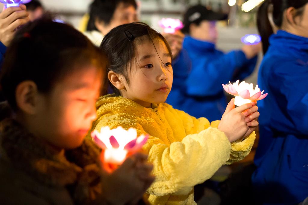 Jovens praticantes da disciplina espiritual do Falun Gong realizam uma vigília de velas perto do consulado chinês em Nova York em protesto contra a brutal repressão e perseguição do regime chinês contra os adeptos na China; em 23 de abril de 2017 (Samira Bouaou/The Epoch Times)
