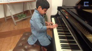 Menino curva-se sobre piano, e quando de repente ele começa a tocar é surpreendente