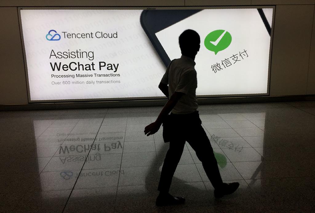 Um homem chinês caminha no aeroporto internacional de Hong Kong enquanto passa por um anúncio da plataforma de mídia social WeChat, de propriedade da Tencent, em 21 de agosto de 2017 (Richard A. Brooks/AFP/Getty Images)