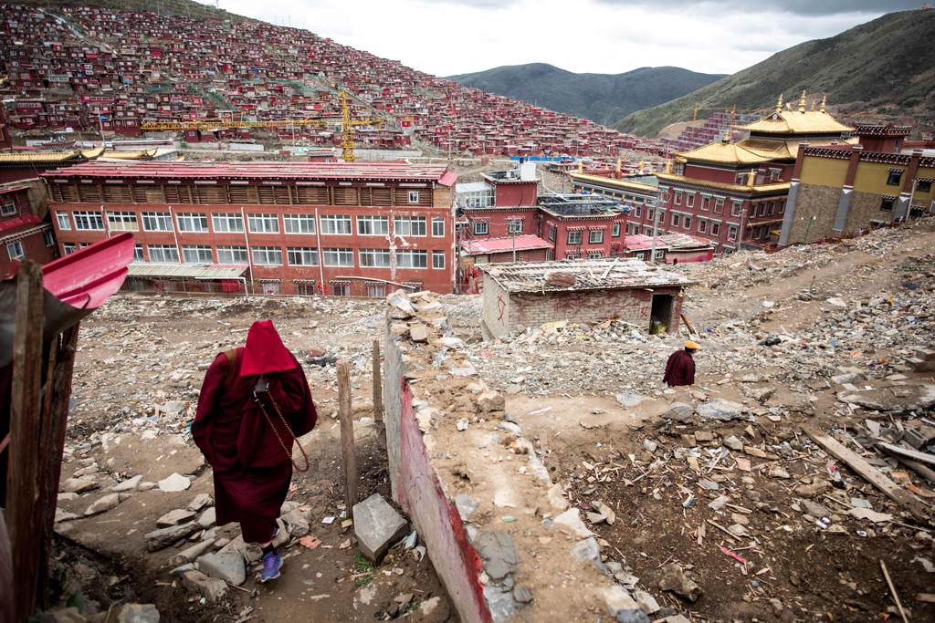 Uma monja caminha entre detritos de casas demolidas na mais importante instituição mundial de ensino do budismo tibetano, o monastério Larung Gar, no condado de Sertar, na província de Sichuan, no Sudoeste da China, em 29 de maio de 2017. O regime chinês ordenou e tem conduzido essas demolições desde 2016 (Johannes Eisele/AFP/Getty Images)