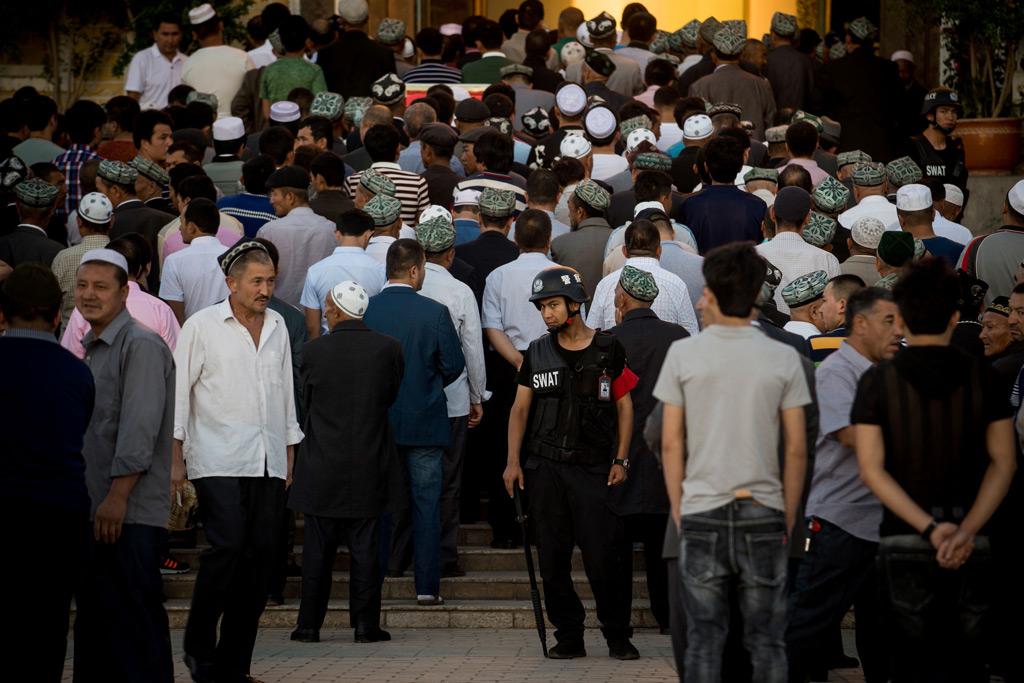 Um policial permanece de prontidão enquanto muçulmanos chegam para a oração da manhã do Eid al-Fitr no mesquita Id Kah em Kashgar, Xinjiang, em 26 de junho de 2017 (Johannes Eisele/AFP/Getty Images)