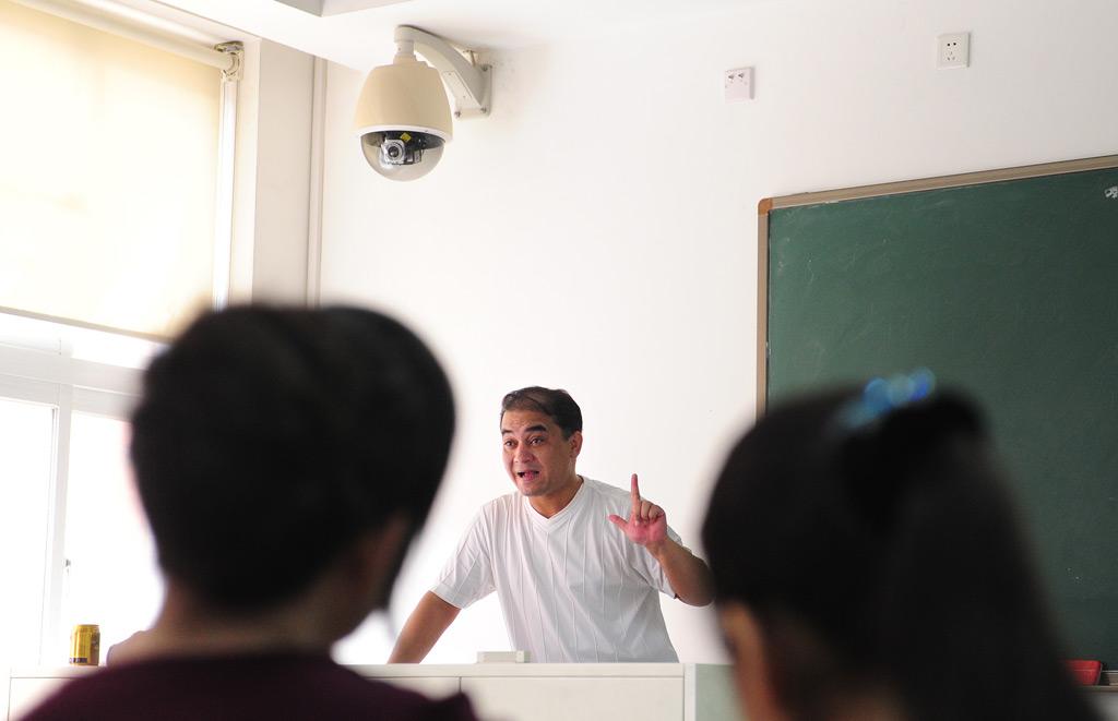 Uma câmera de vigilância de segurança montada sobre o pódio do professor enquanto o docente universitário Ilham Tohti leciona numa sala de aula em Pequim, China, em 12 de junho de 2010 (Frederic J. Brown/AFP/Getty Images)