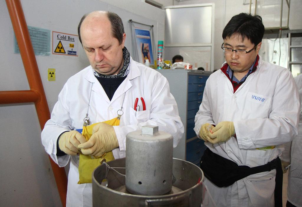 Inspetores da Agência Internacional de Energia Atômica (AIEA) não identificados desconectam as conexões entre equipamentos para produção de urânio altamente enriquecido na usina nuclear de Natanz (Kazem Ghane/AFP/Getty Images)