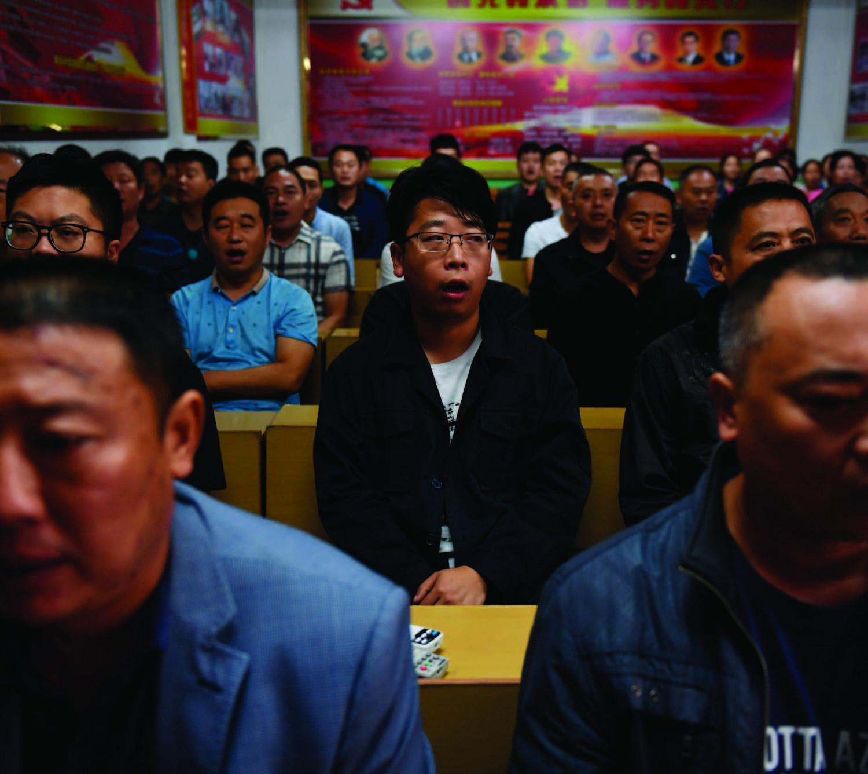 Gerentes de fábricas cantam canções vermelhas comunistas no início do seu dia de trabalho no vilarejo de Nanjie, na região central da província de Henan, em 27 de setembro de 2017 (Greg Baker/AFP/Getty Images)