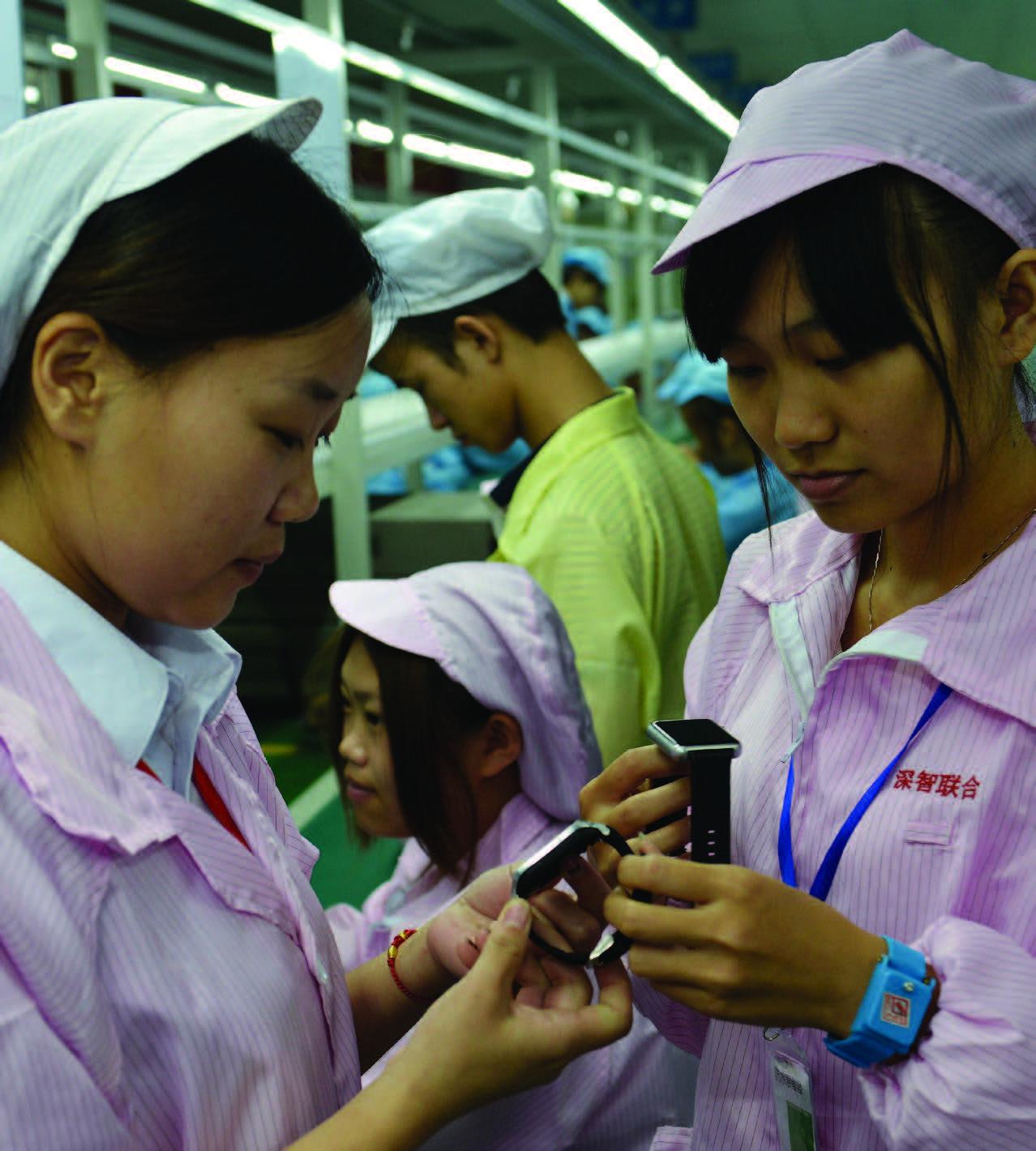 Trabalhadores chineses posam com uma alternativa local mais barata do Relógio Apple em Shenzhen, na província de Guangdong, sul da China, em 22 de abril de 2015 (STR/AFP/Getty Images)