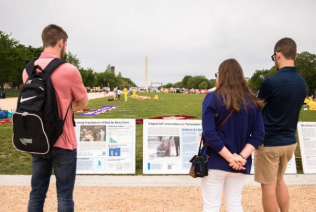 Pessoas observam bandeiras que representam o Falun Dafa durante a comemoração do Dia do Falun Dafa no National Mall em Washington, em 5 de maio de 2018 (Samira Bouaou/Epoch Times)