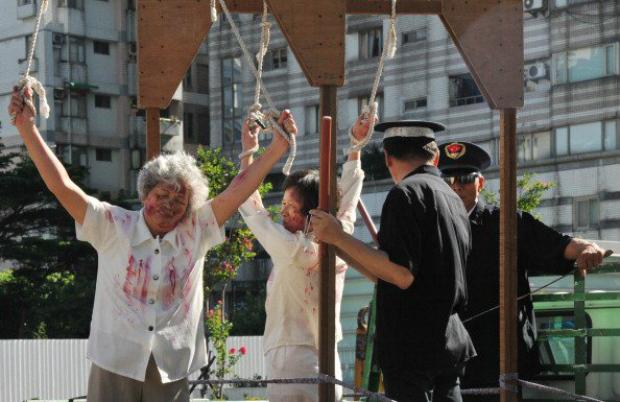 Praticantes do Falun Dafa representam uma cena de tortura, largamente praticada pela polícia chinesa contra os praticantes, durante manifestação em protesto contra a perseguição do regime chinês, ocorrida em Taipei, Taiwan, em 20 de julho de 2014 (Mandy Cheng/AFP/Getty Images)