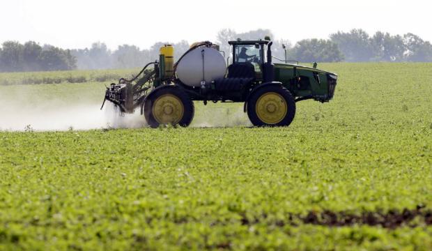 Blake Beckett, da cooperativa West Central, pulveriza um campo de soja em Granger, Iowa, em 11 de julho de 2013 (Charlie Neibergall/AP)