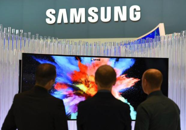 """No dia da inauguração da feira de eletrônicos de consumo """"Internationale Funk Ausstellung"""" em Berlim, na Alemanha, em 5 de setembro de 2014, visitantes observam um televisor de tela curva exibido em um stand da Samsung (Tobias Schwarz/AFP/Getty Images)"""