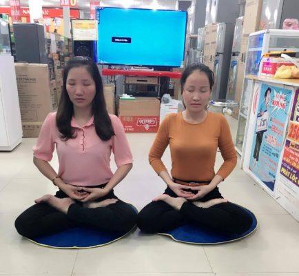 A autora (dir.) e outra praticante do Falun Dafa fazendo o exercício de meditação da disciplina.