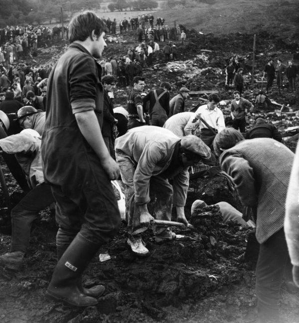 Equipes de resgate limpando destroços e lama em 22 de outubro de 1966, perto da escola Pantglas Junior em Aberfan, em Gales do Sul, onde uma ponte de carvão desmoronou matando muitas crianças (Keystone/Getty Images)