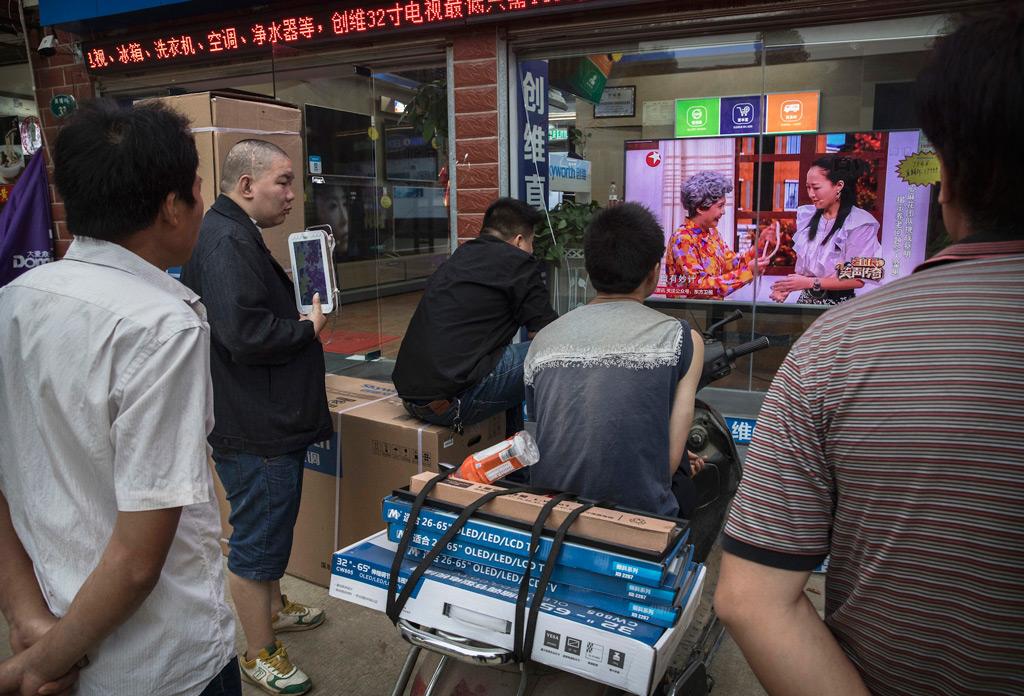 Homens assistem a um programa numa televisão na vitrine de uma loja de eletrônicos na cidade de Wuhan, província de Hubei, em 15 de maio de 2017 (Kevin Frayer/Getty Images)