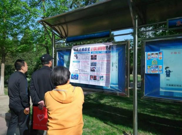 Lendo informações sobre o Falun Dafa em um quadro de avisos (Minghui.org)