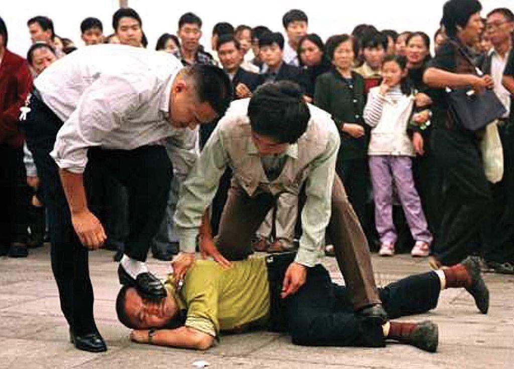 """Policiais chineses à paisana portando uma faca tentam """"silenciar"""" um praticante do Falun Dafa (ou Falun Gong) na China (Epoch Times)"""