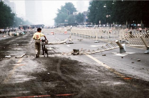 Pequim, China — 04/06/1989: ao fim do movimento pró-democracia na China, um ciclista solitário cruza as barreiras da Avenida Changan esmagadas por tanques do exército chinês durante a noite de violência na Praça Tiananmen e arredores. Depois de semanas de protestos, horas antes desta foto ser tirada, o regime comunista realizou sua última repressão brutal sobre os manifestantes (Peter Charlesworth/LightRocket/Getty Images)