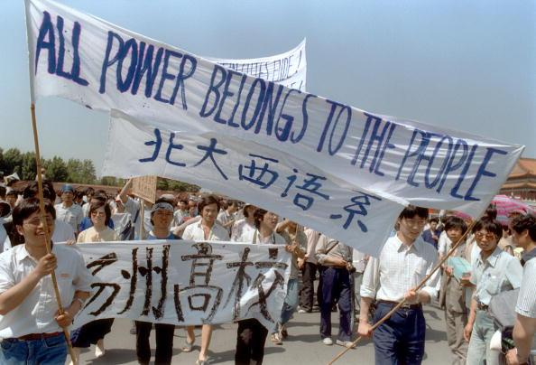Pequim, China — 25 de maio: Agitando bandeiras, estudantes do ensino médio marcham nas ruas de Pequim perto da Praça Tiananmen, em 25 de maio de 1989, durante um protesto pró-democracia contra o regime chinês (Catherine Henriette/Getty Images)