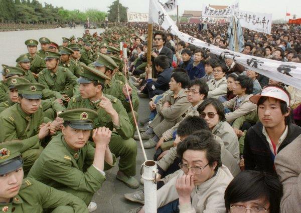 22 de abril de 1989: várias centenas dentre os 200 mil manifestantes pró-democracia ficam frente a frente com soldados do lado de fora do Grande Salão do Povo na Praça Tiananmen, em Pequim, durante cerimônia fúnebre do ex-líder do Partido Comunista Chinês e reformista liberal Hu Yaobang (Catherine Henriette/Getty Imagaes)