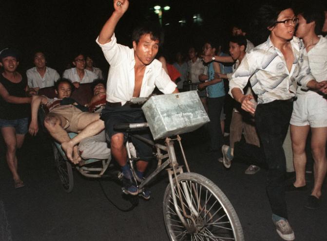 Esta foto de 4 de junho de 1989 mostra o transporte de duas pessoas feridas durante o ataque do exército contra os estudantes próximo à Praça Tiananmen (Manuel Ceneta/AFP/Getty Images)