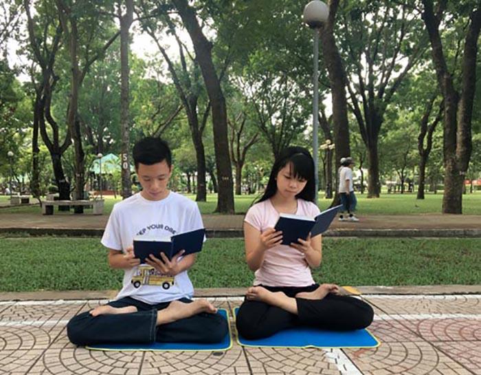 """Os dois filhos de Lanh também leem regularmente o livro """"Zhuan Falun"""" do Falun Dafa. Depois de testemunhar o poder transformador do Falun Dafa, eles também começaram a cultivar diligentemente (DKN.tv)"""