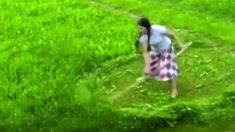 Mulher corta grama rapidamente com apenas uma foice