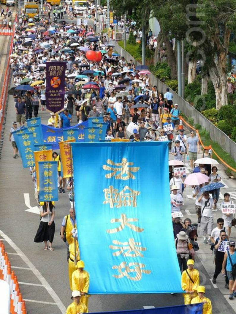 """Praticantes do Falun Gong carregam uma bandeira azul gigante com as palavras """"Falun Dafa é bom"""", em um desfile em Hong Kong em 1º de julho de 2018 (Epoch Times)"""