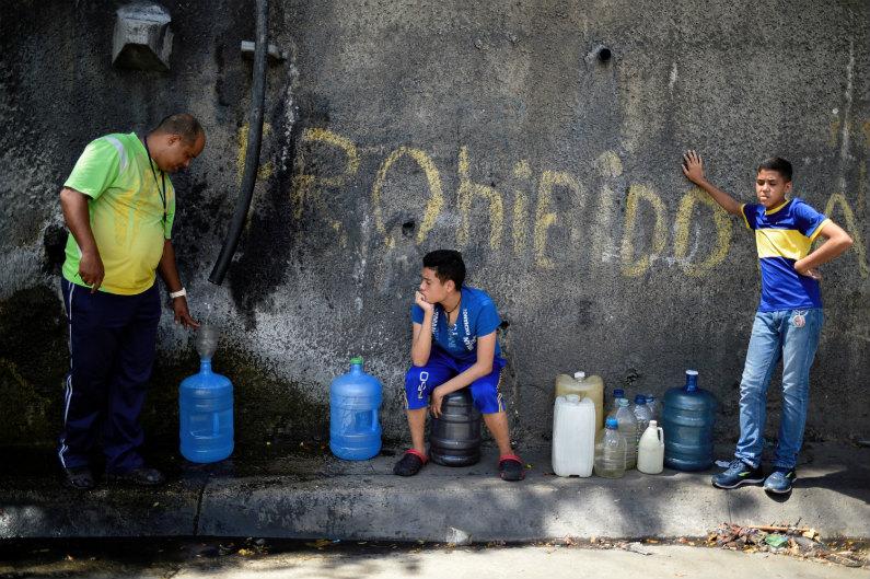Pessoas fazem fila para encher garrafões com água da montanha Wuaraira Repano em 13 de junho de 2018 em Caracas, Venezuela, onde a esmagadora crise econômica e política causou escassez generalizada de água, alimentos e medicamentos básicos (Federico Parra/AFP/Getty Images)