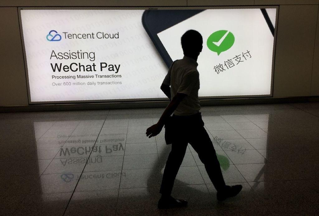 Homem no Aeroporto Internacional de Hong Kong passa por um anúncio da plataforma de redes sociais WeChat, de propriedade da empresa Tencent, em 21 de agosto de 2017 (Richard A. Brooks/AFP/Getty Images)