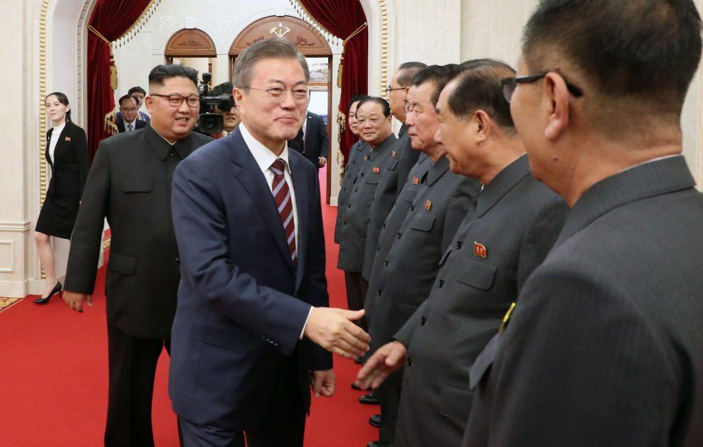 Presidente sul-coreano Moon Jae-in aperta a mão de funcionários norte-coreanos, enquanto o líder norte-coreano Kim Jong-un observa, antes da reunião de 18 de setembro de 2018 em Pyongyang, na Coreia do Norte (Pyongyang Press Corps/Getty Images)